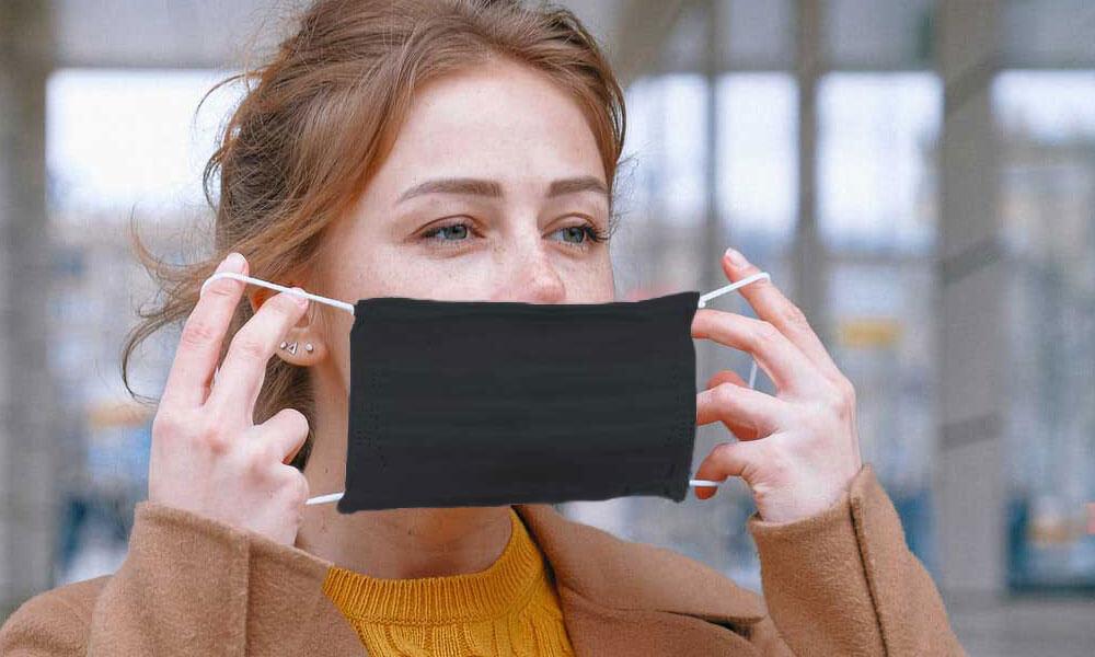 Femme portant à son visage un masque COVID-19 gris foncé